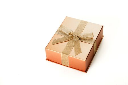 Beautiful box for a gift with a bow from a gold ribbon on a white background close-up Stok Fotoğraf
