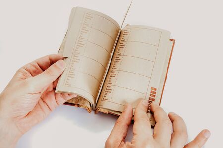 Hands of a man leafing through pages of a notebook with an alphabetical index with sheets of yellow thick paper close-up
