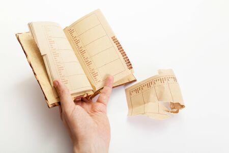 left hand of a man holds an open book with an alphabetical index. Nearby lies a torn sheet