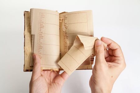 Man right hand pulls a page out of the middle of an notebook with an alphabetical index