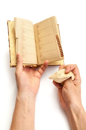left hand of a man holds an open book with an alphabetical index. The right hand wrinkles the torn sheet