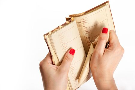 emotional act. Female hand with red manicure tears a page out of a notebook with an alphabetical index
