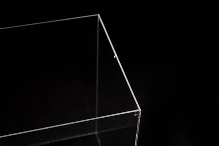 Geometric abstraction. The corner of a transparent parallelepiped made of organic glass stands on a black background Stock Photo