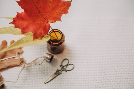 Autumn leaves and scissors. A beautiful red maple leaf stands in a dark glass jar. Graceful scissors and a thimble lie nearby. View from above Фото со стока - 131386137