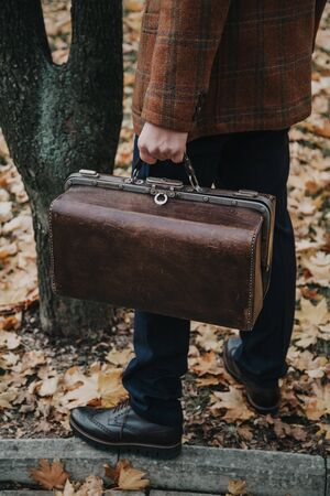man in a stylish checkered jacket carries a retro brown leather bag in an autumn park close-up