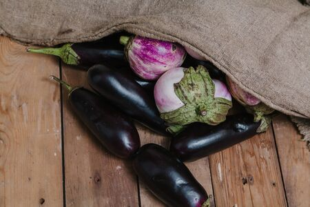canvas bag lies on planed boards. Nearby lies a bunch of blue eggplants and light lilac eggplant sort of bumbo Stok Fotoğraf