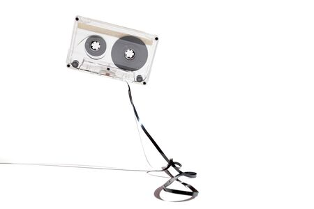 Audio cassette for tape with a transparent plastic case on a white background close-up. A loop of film lies in front of the cassette.