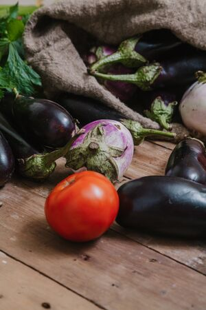 Set of vegetables on the boards. Eggplant of different varieties, red tomatoes and large stalks of celery are on wooden boards. Nearby lies a canvas bag