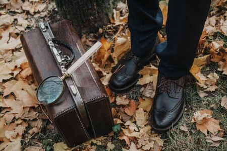 Detective in the autumn park. A leather carpetbag is standing on fallen maple leaves. Above is a large magnifier on a long handle. Nearby are the legs of a man in stylish shoes.