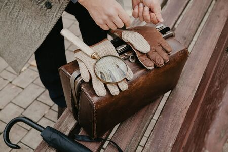 antique leather carpetbag is standing on a bench in an autumn park. On top are gloves and a magnifying glass on a long handle. In the background, a detective in a light coat Banco de Imagens