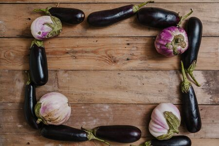 Ripe blue eggplants are laid out in the form of a rectangular frame. On planed wooden boards. In the corners are laid round white lilac eggplant varieties of bumbo Stok Fotoğraf