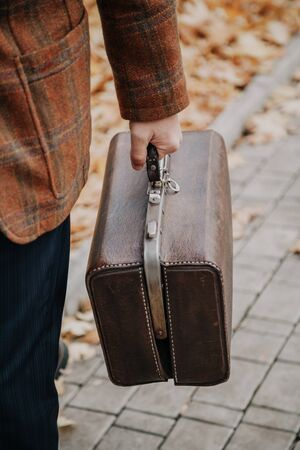 man in a stylish plaid jacket carries a retro brown leather bag close-up  스톡 콘텐츠