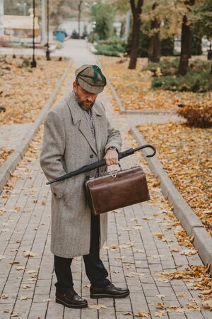 man with a beard in a gray coat and cap is standing on a narrow alley of an autumn park. In the hand an umbrella-cane and a valise