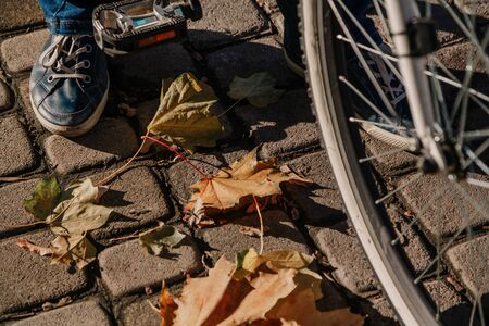 right leg in a blue leather sneaker stands on a square paving slab. Near a bicycle wheel and pedal. Lying yellow fallen leaves