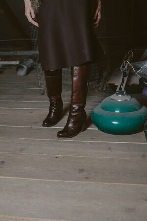 slender girl in high leather boots stands on planed wooden boards. The left hand rests on the knee  Imagens