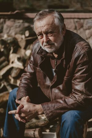 Portrait of a man with a gray beard. Old man in a leather jacket and cap close-up autumn day