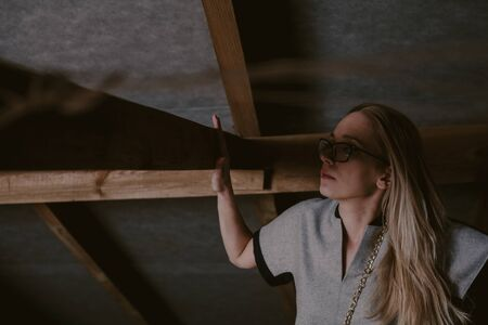 Portrait of a blonde in the attic. A pretty slender blonde stands in the attic against a brick wall. And leans on a wooden beam  Imagens