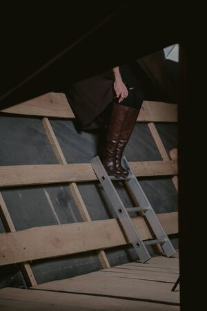 slender girl in high leather boots stands on planed wooden boards. The left hand rests on the knee