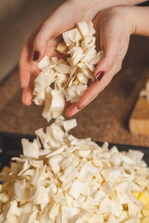 Cooking vegetable stew. Hands with manicure sprinkles chopped cabbage on a black metal pan closeup Zdjęcie Seryjne - 133092859