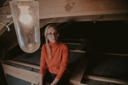 Pretty blonde in an orange sweater sits on wooden boards in the attic. Raised legs high in leather boots