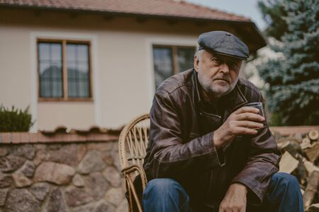 Portrait of a handsome man with a beard. An elderly man in a leather jacket and cap holds a glass of whiskey in his hand. At the back of a modern private house Imagens