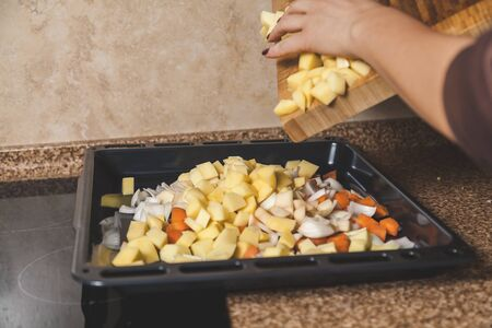 Cooking vegetable stew. Hand pours chopped potatoes from a cutting board onto a black metal pan