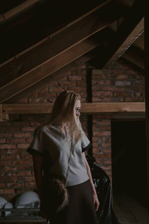Portrait of a blonde in the attic. A pretty slender blonde stands in the attic against a brick wall. And leans on a wooden beam