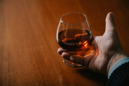 right hand holds a glass goblet with cognac on a brown background