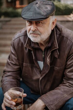 Portrait of a respectable man. An elderly man with a beard in a leather jacket and cap holds a glass of whiskey in his hand. In the background a pile of firewood