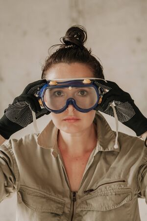 Nice girl in gray overalls and black gloves looks right through plastic glasses. Portrait of a woman without retouching with her natural imperfections