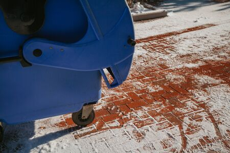blue mobile trash bin stands on a red paving slab covered with white snow. Tank cap open