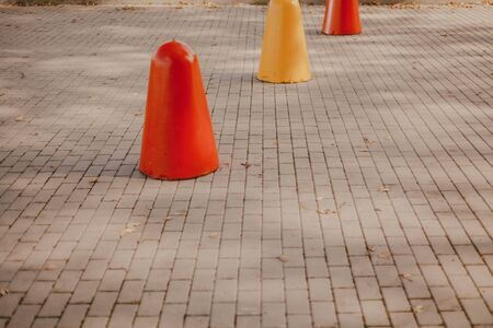 number of red and yellow cast-iron pedestals for parking vehicles stands on the sidewalk tile Imagens