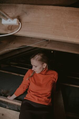 pretty blonde in glasses and an orange sweater sits on wooden boards in the attic Imagens