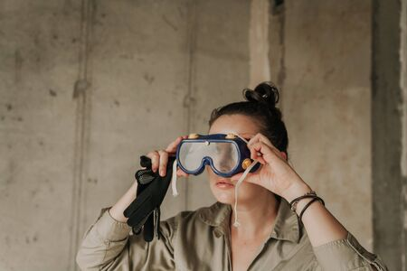 Nice girl in a gray overalls at a construction site puts on plastic safety glasses. Female portrait without retouching with her natural imperfections.  Imagens