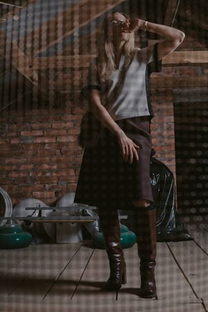 Beauty and the tank. A pretty slender blonde in leather boots stands on wooden boards in the attic against a brick wall. In front of it is a blurry grid