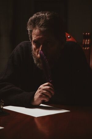 man with a beard sits at a large polished table and reflects on a white sheet. In the hand is a goose feather. Nearby is a metal inkwell