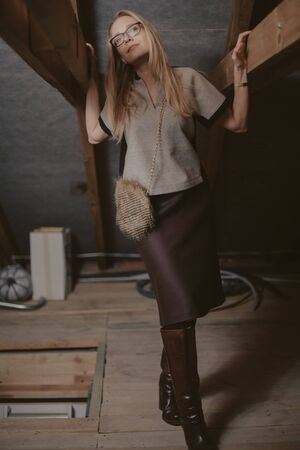 pretty slender blonde stands between the wooden rafters in the attic. Stylish handbag hanging on a chain over his shoulder Imagens