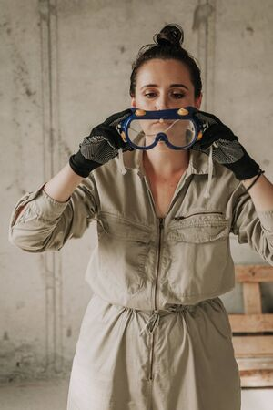Nice girl in a gray overalls at a construction site puts on plastic safety glasses. Female portrait without retouching with her natural imperfections.