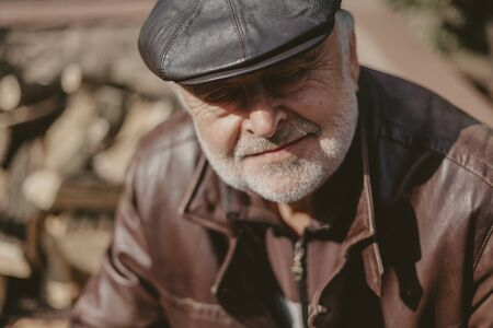 Portrait of a man with a gray beard. Old man in a leather jacket and cap close-up autumn day Imagens