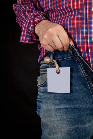 Hands in a red plaid shirt fasten blue jeans. A gray paper label weighs on a loaf on a thick rope with a tag