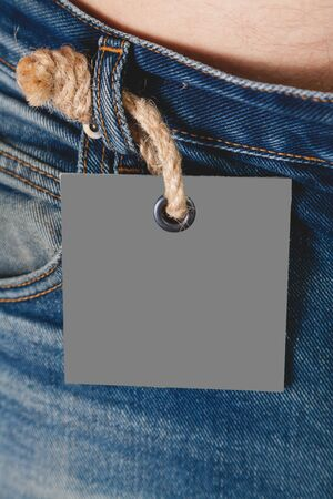 gray paper label hangs on a loafer of jeans on a thick rope with a large knot