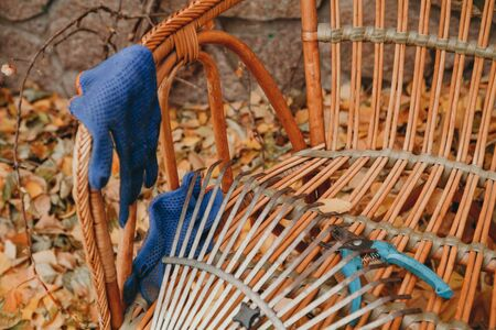 Autumn still life. A fan rake and garden shears lie on a beautiful wicker chair in an autumn park. Nearby are blue gloves. Close-up