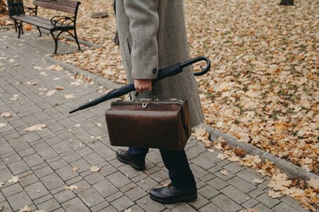 gentlemans walk. A man in stylish shoes and a white coat walks along the narrow alley of the autumn park. In the hand an umbrella-cane and a valise 版權商用圖片