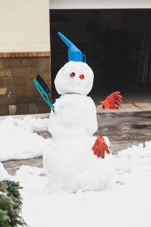 Snowman motorist stands in front of the garage. For decoration use a watering can, a brush and working gloves Stock Photo