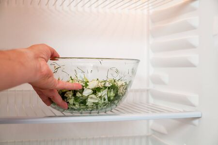 Healthy food. The hand of a vegan takes a glass bowl with chopped vegetables on the shelf of an empty refrigerator close up. Stock Photo
