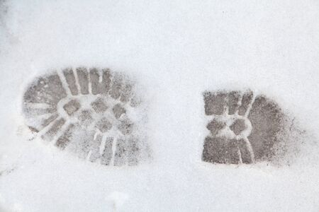 Footprints in the snow. Clear tread imprint on the sole of the boot on white snow Reklamní fotografie