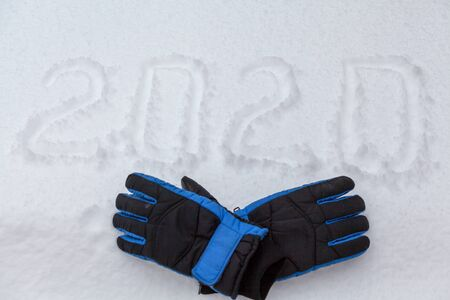 New Year on the street. 2020 written on white snow. Nearby are warm gloves Reklamní fotografie