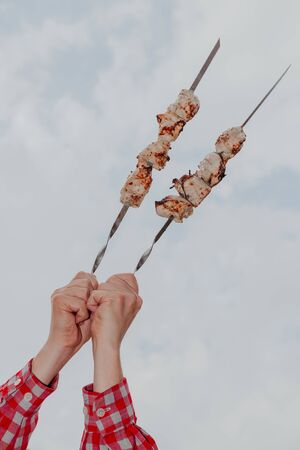 Barbecue in the sky. Hands hold two steel skewers with fried meat on a background of cloudy sky