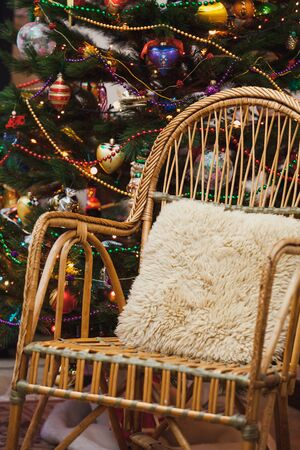 beautiful wicker chair stands in front of a decorated Christmas tree. There is a small sheepskin pillow on the armchair