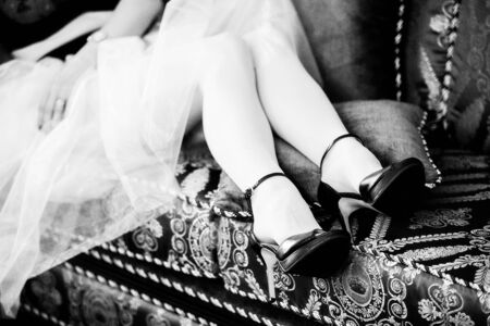Slender female legs in black shoes with thin high heels and white stockings are lying on a pillow on a soft sofa close-up